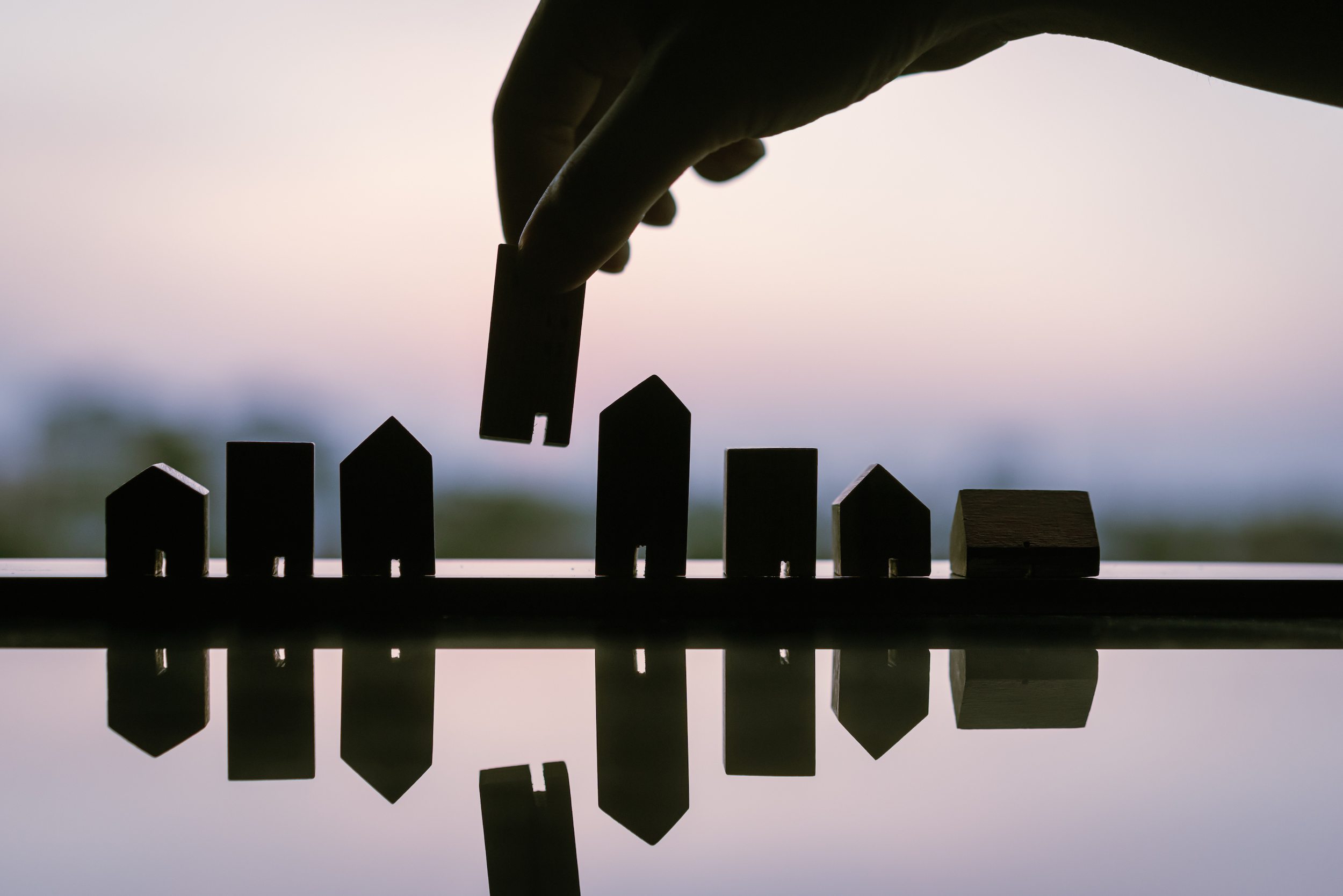 Silhouette of hand choosing mini wood house model from model and row of coin money on wood table, selective focus, Planning to buy property. Choose what's the best. A symbol for construction ,ecology. (Silhouette of hand choosing mini wood house model